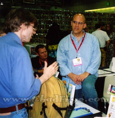"I hung out at the National Cartoonists Society (NCS) booth quite a bit. Here are Richard Thompson (cartoonist of ""Cul-de-sac"") is chatting with John Kovaleski (who was selling collections of his ""Bonanas"" comic)."