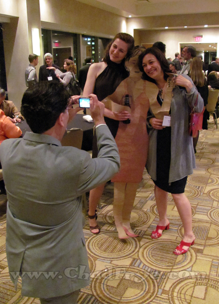 "Illustrator Sean Kelly taking a photo of Kate Reilly and Wendy Peng posing with a paper cut-out of Paul Gilligan's (""Pooch Cafè"") girlfriend (made by ""Secret Saturday's"" Jay Stephens) who couldn't make it past Canadian customs."