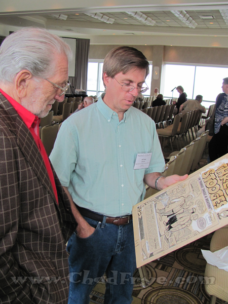 "Joe Kubert looking on as Bill Janocha (assistant to Mort Walker) show Joe an original splash page of ""The Three Stooges"" comic book that Joe drew in younger days."
