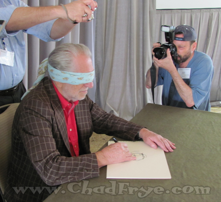 David Folkman has been collecting artist drawings created while blindfolded. Here he takes Joe Kubert's picture as he attempts to draw his character Tor.