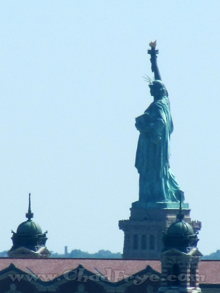 A nice closer view of The Statue of Liberty with a little of the main building on Ellis Island in the foreground.